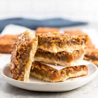 Pecan pie bars stacked on a plate.
