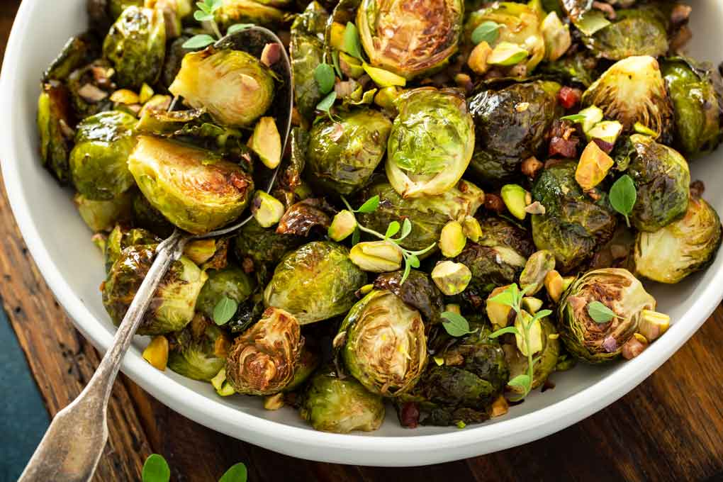 Spoon scooping oven baked caramelized Brussels Sprouts with bacon.