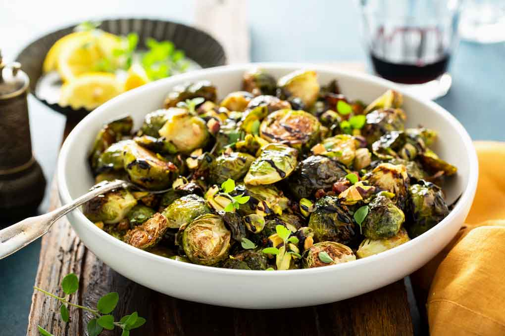 Roasted sprouts drizzled with balsamic syrup and pistachios