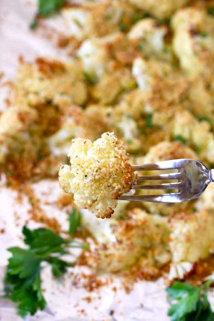 Close up view of oven roasted cauliflower floret lift with a fork