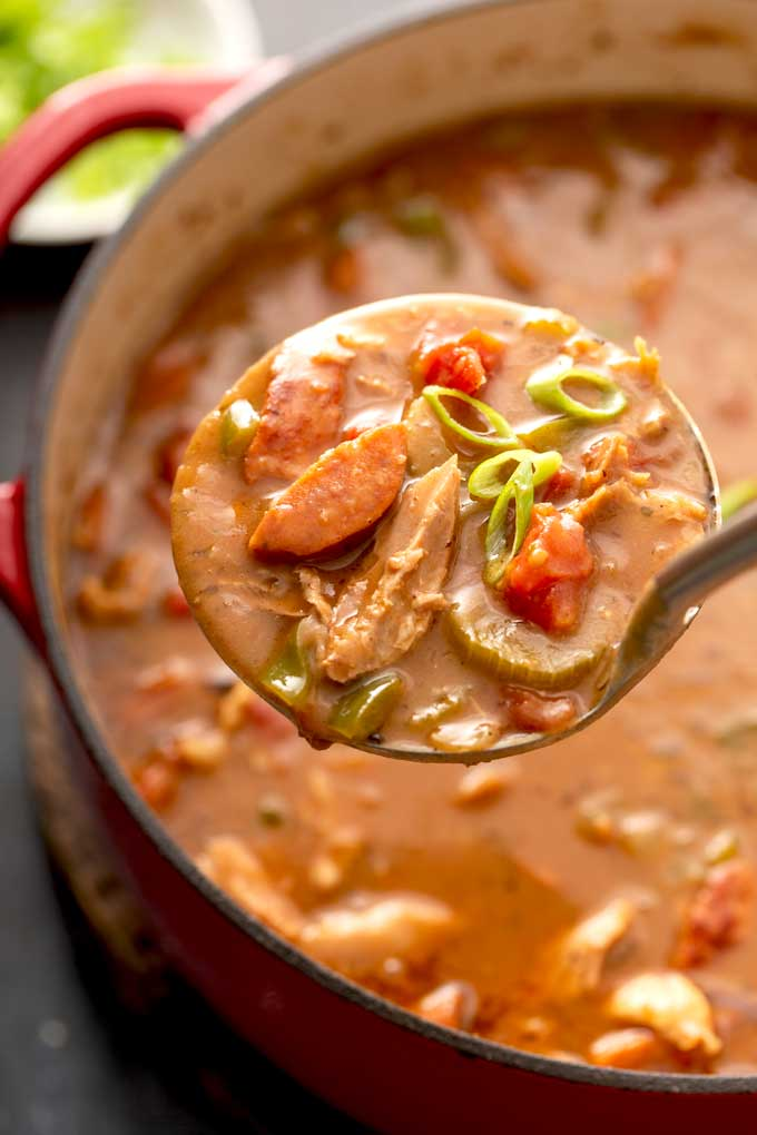 A ladle full of sausage and turkey gumbo getting served from a pot