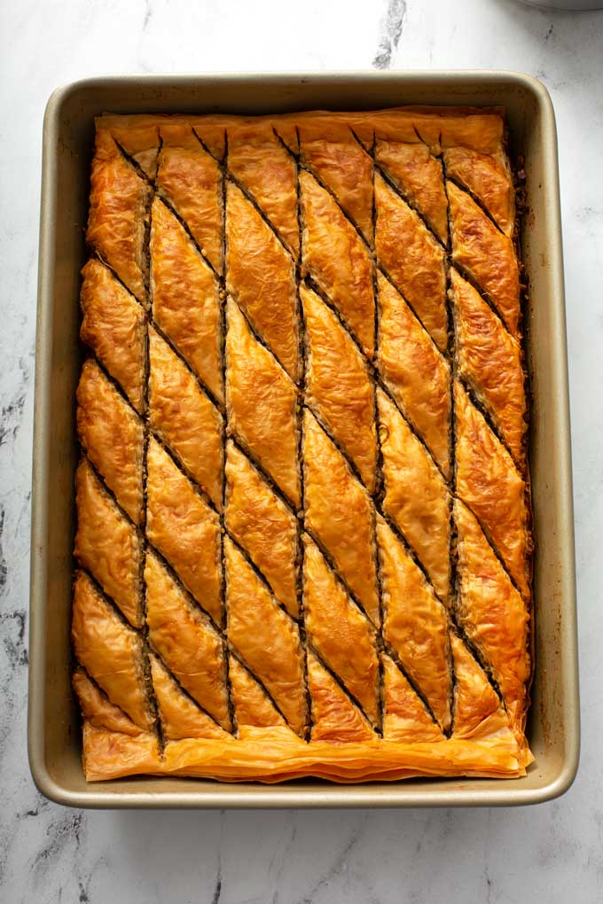 Golden brown baked baklava in a baking pan.