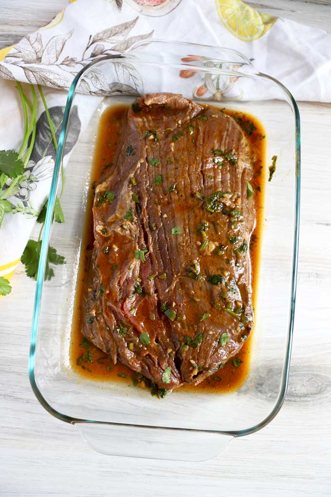 Flank steak marinating in a glass dish.