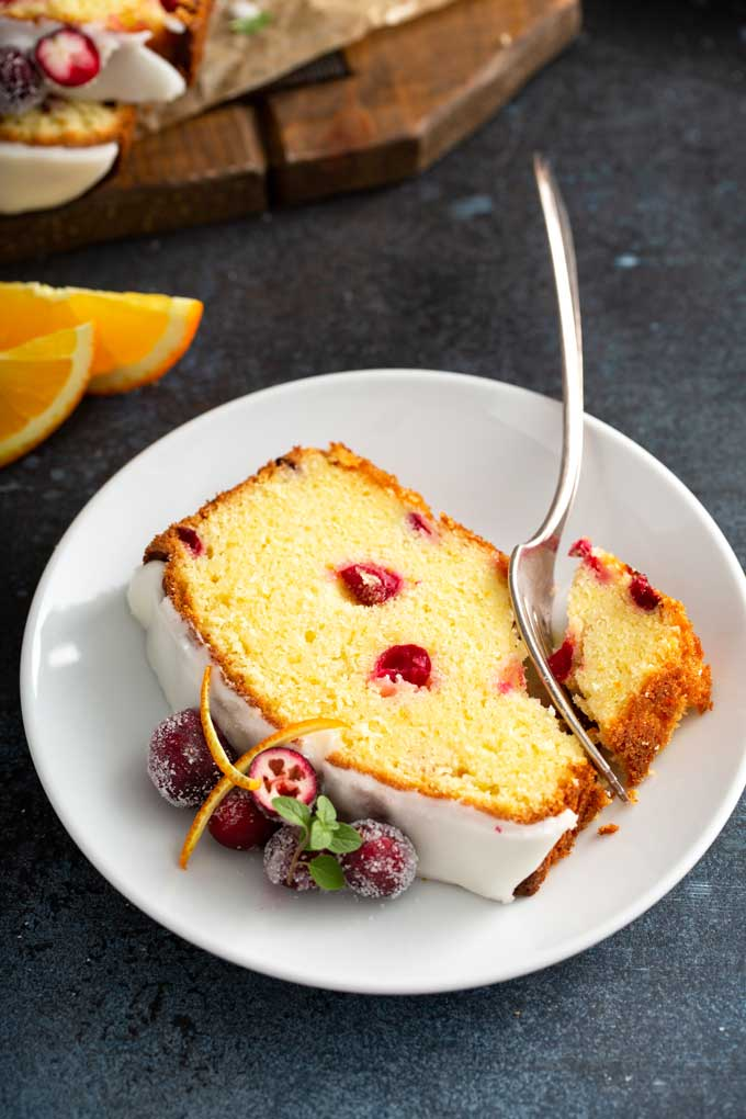 A slice of cranberry orange bread on a white plate