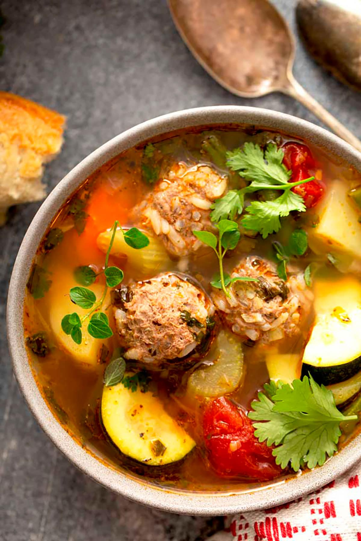 Close up view of Albondigas soup with vegetables in a white bowl
