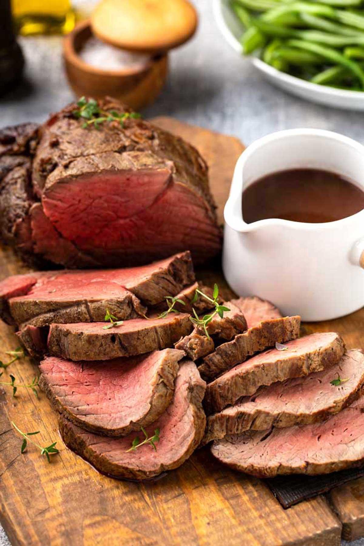 A beef tenderloin roast sliced on a carving board.