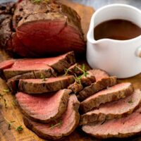 Sliced beef tenderloin on a wooden board next to a small white pitcher with wine sauce