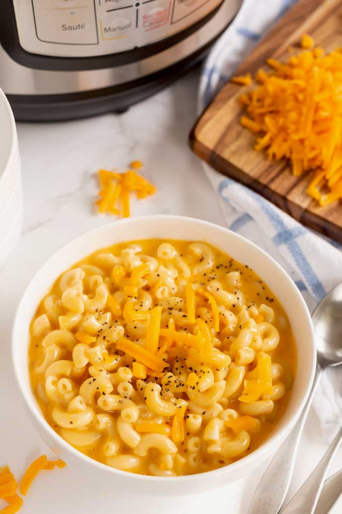 A bowl of mac and cheese next to a pressure cooker.