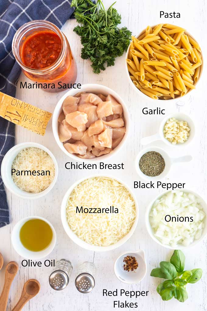 Ingredients to make Chicken Parmesan Pasta on a white wooden surface.