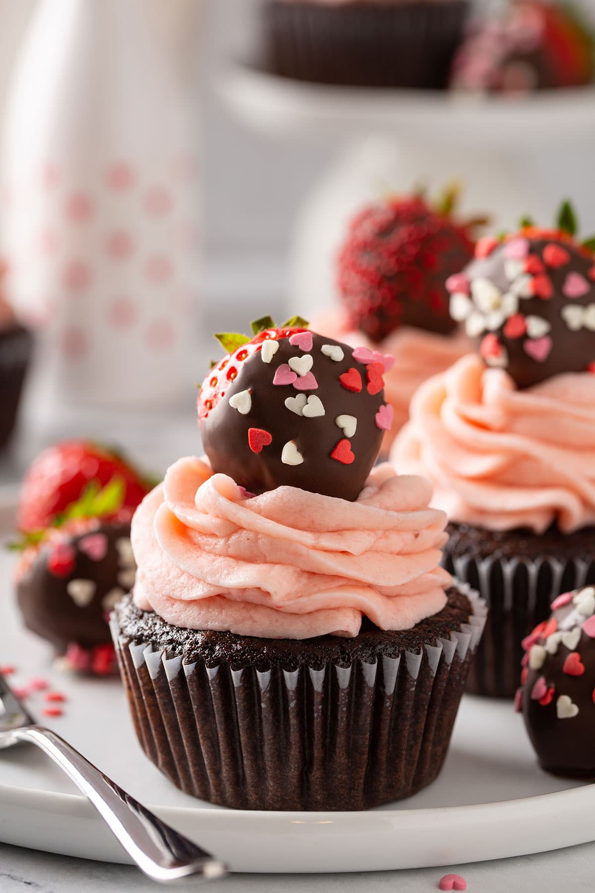 Close up to a cupcake topped with a chocolate covered strawberry