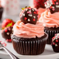 Chocolate cupcakes covered with strawberry frosting and a chocolate covered strawberry