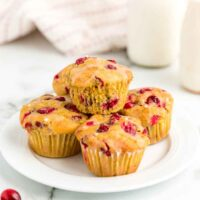 Stack of cranberry orange muffins on a white plate
