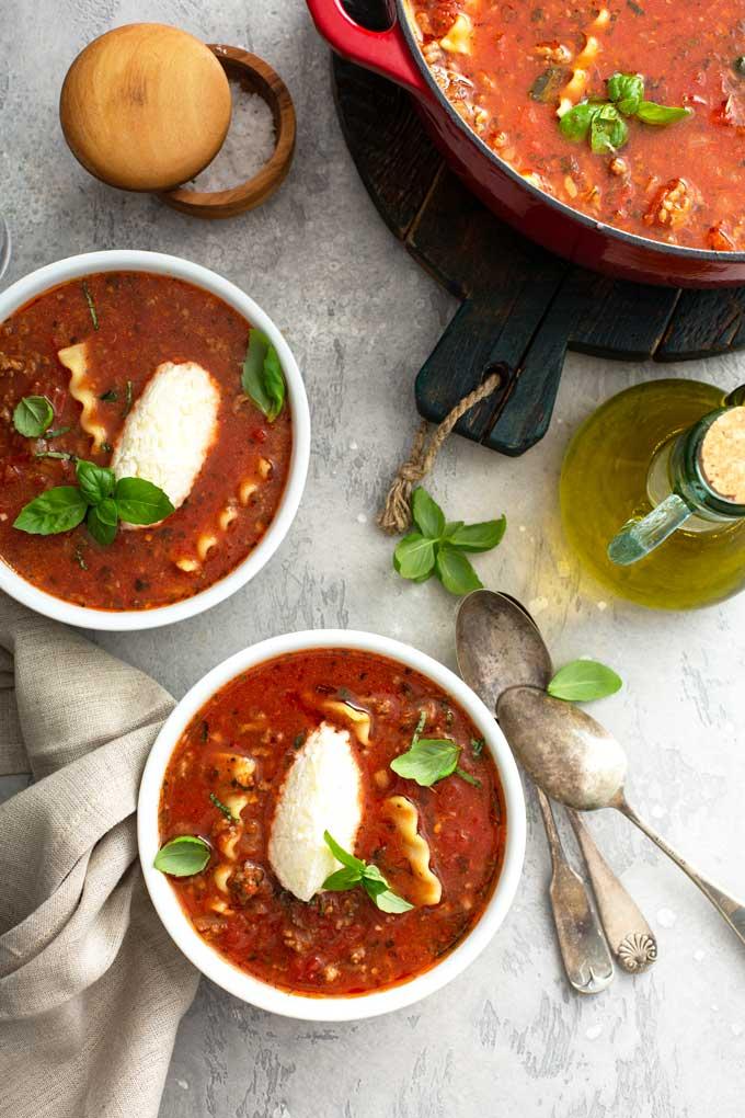 Bowls of lasagna soup next to a pot of soup.