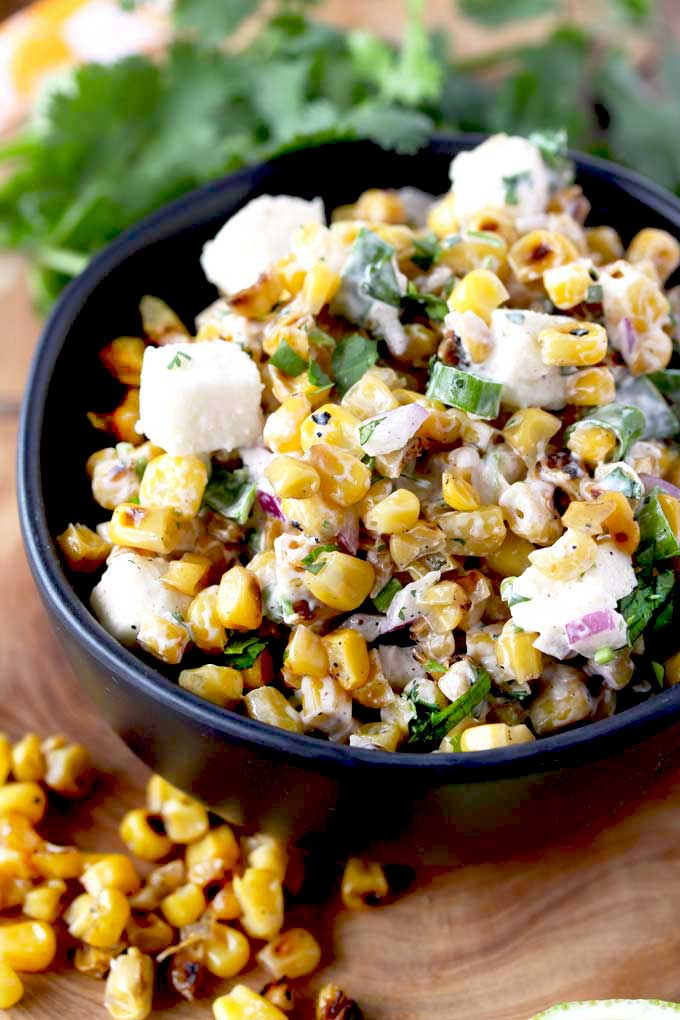 A black salad bowl filled with creamy roasted corn salad