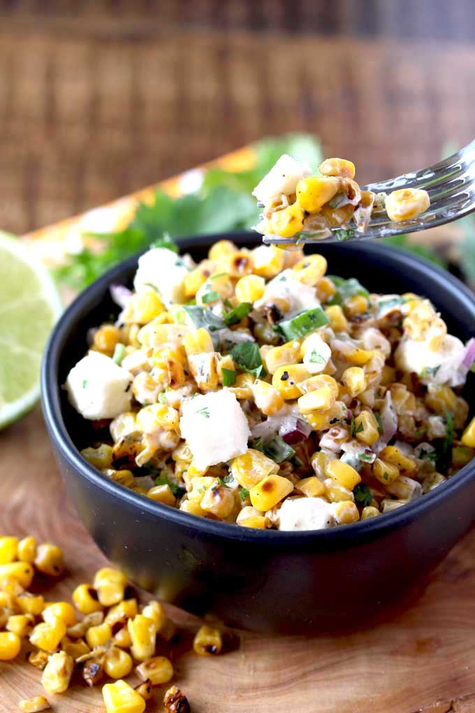 A fork lifting roasted corn salad from a salad bowl