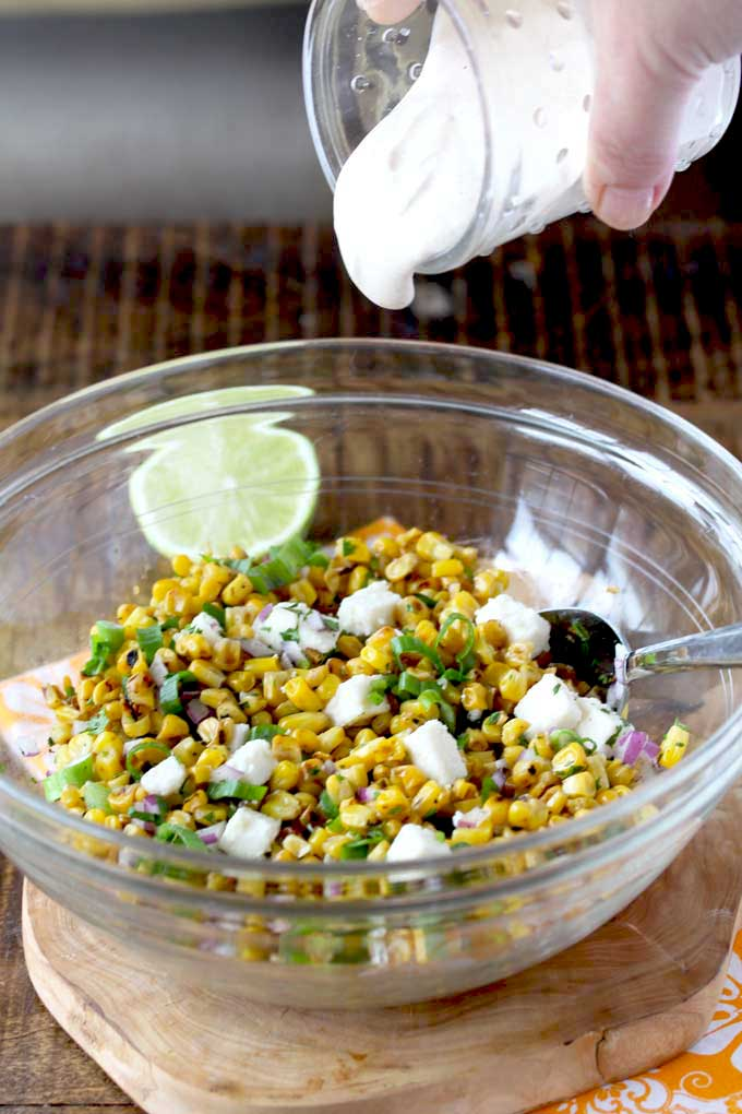 Creamy dressing pouring over corn salad