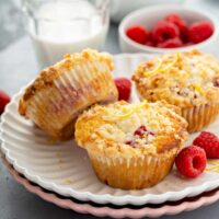 Three raspberry muffins with buttery lemon crumb topping on a plate