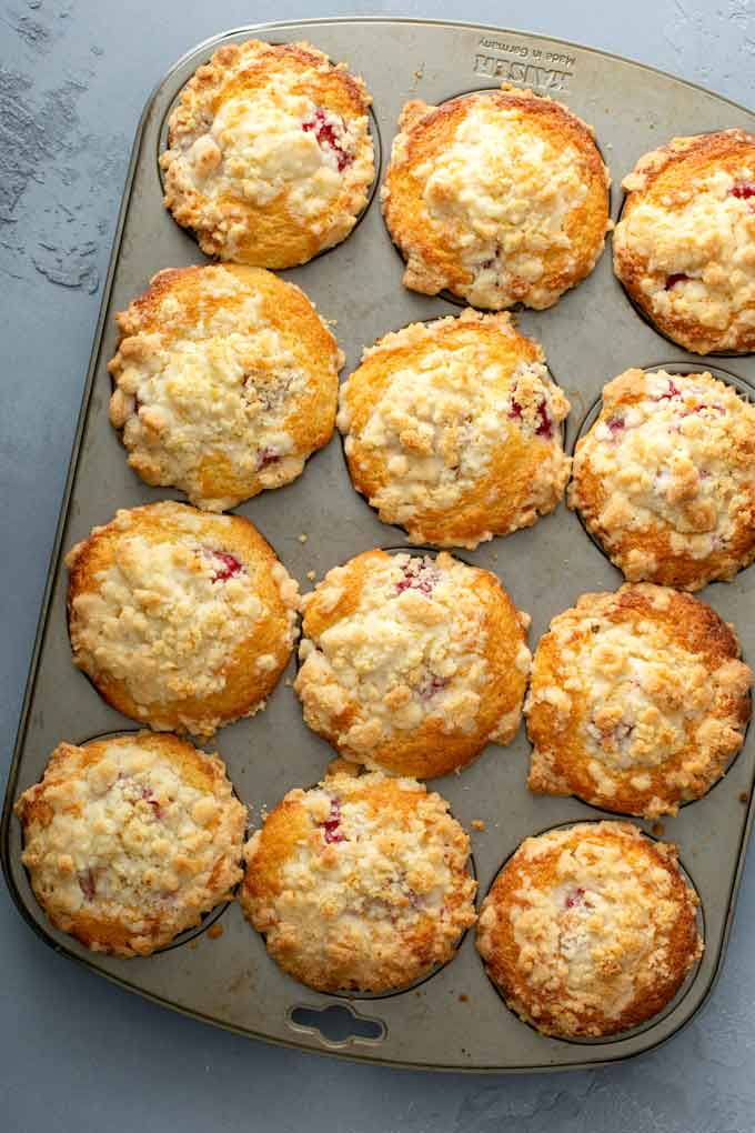 Freshly baked Raspberry muffins with crumb streusel topping in a muffin tin