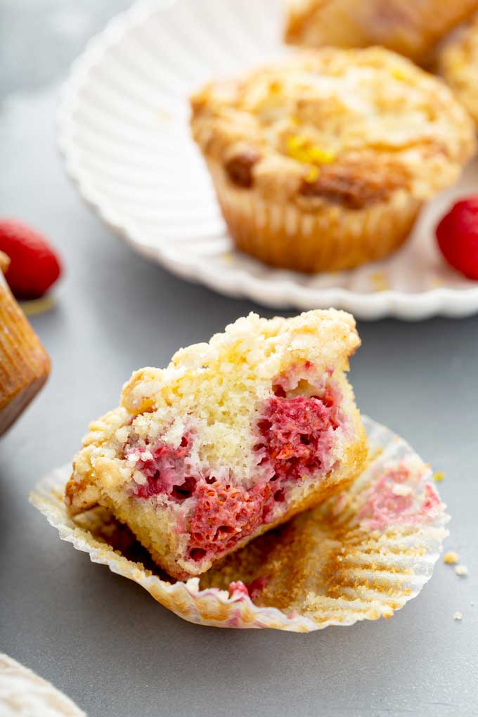 Half of a muffin showing the tender crumb and raspberries