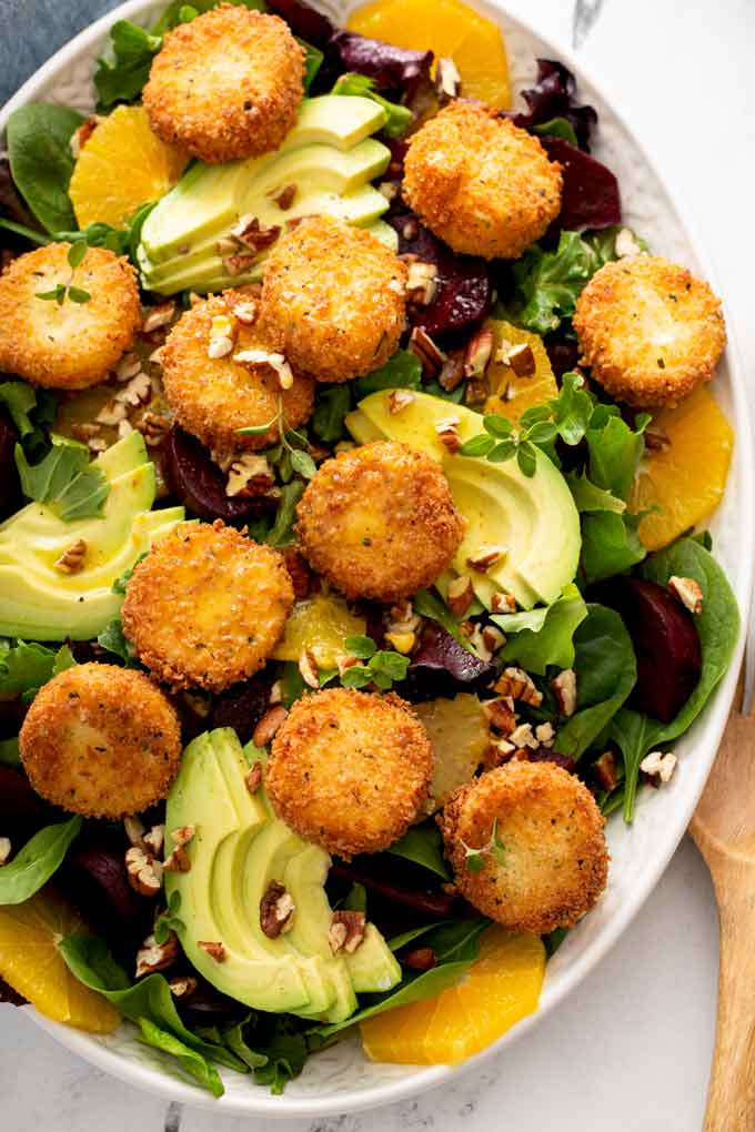 Roasted Beet salad topped with crispy goat cheese on a white platter.
