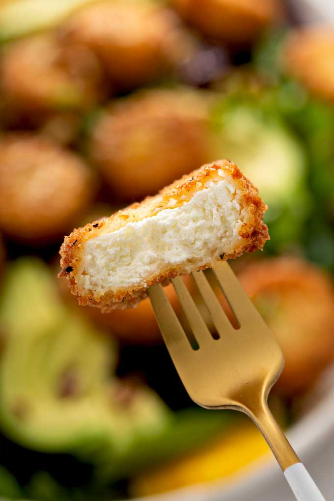 Close up of fried goat cheese cut in half and showing the creamy interior and the crispy coated exterior.