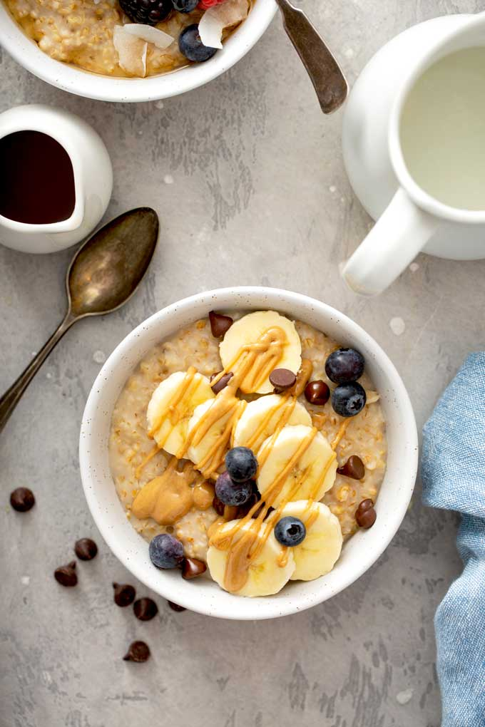 Oatmeal topped with bananas, chocolate chips, blueberries and peanut butter