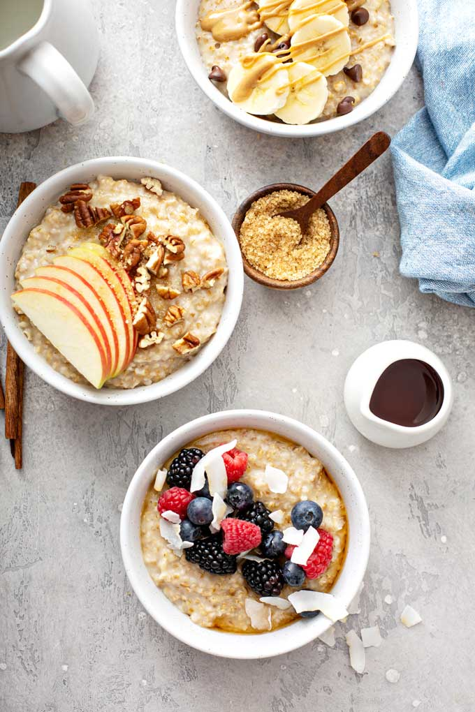 Three bowls of instant pot steel cut oatmeal topped with assorted fruit.