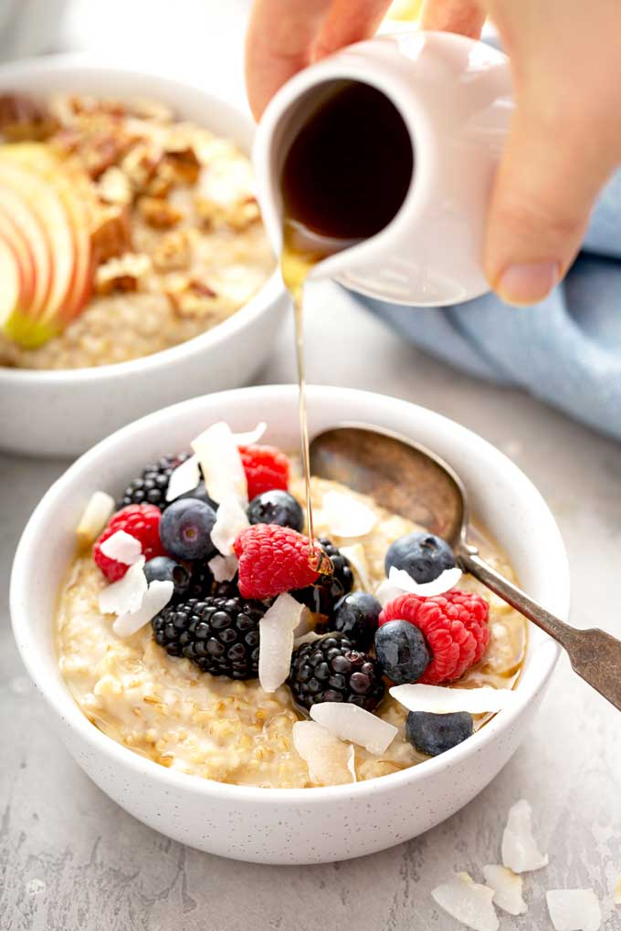 A bowl of steel cut oatmeal topped with berries drizzled with maple syrup