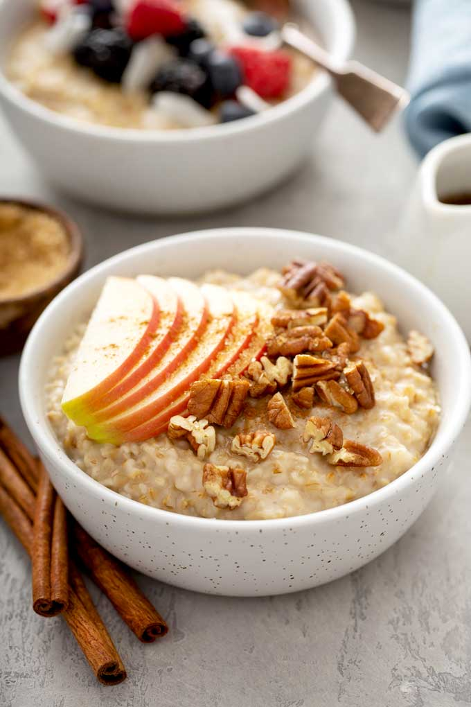 A bowl of breakfast oatmeal cereal topped with sliced apples, brown sugar and pecans
