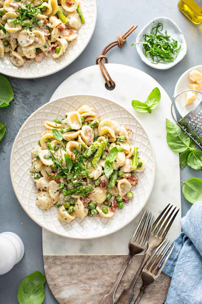 A couple of plates with creamy pasta with asparagus and peas.
