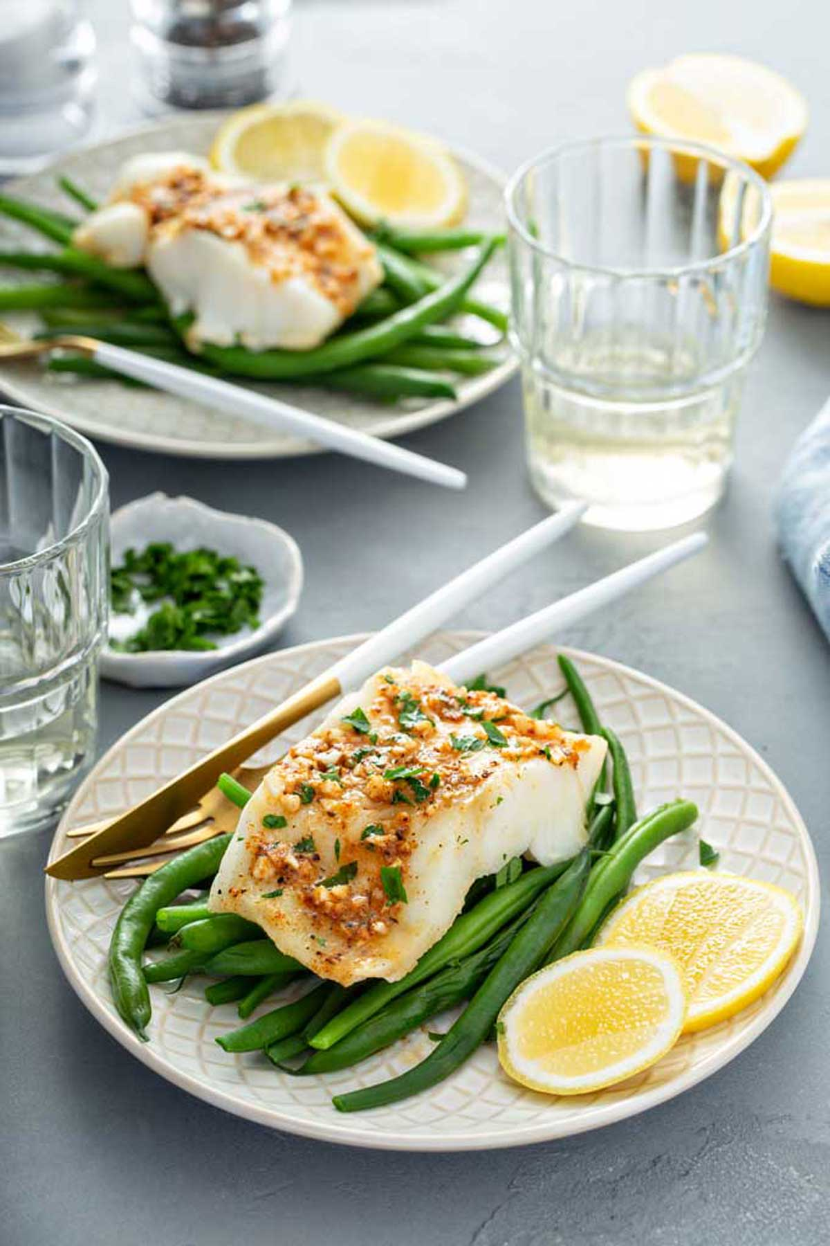 Baked fish cod served with green beans and lemon slices on an ivory plate