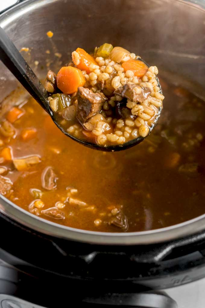 A big scoop of beef soup with barley from an instant pot