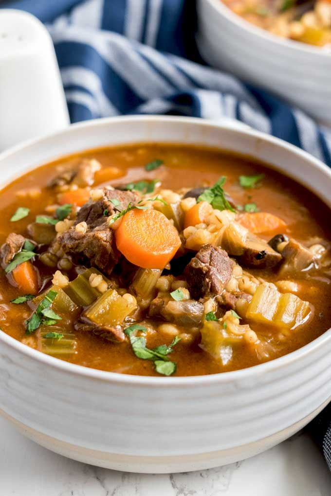 White bowl filled with beef and barley soup