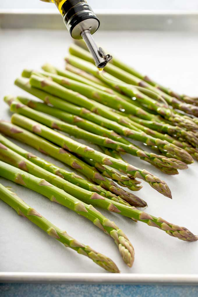 Asparagus on a sheet pan getting drizzled with olive oil
