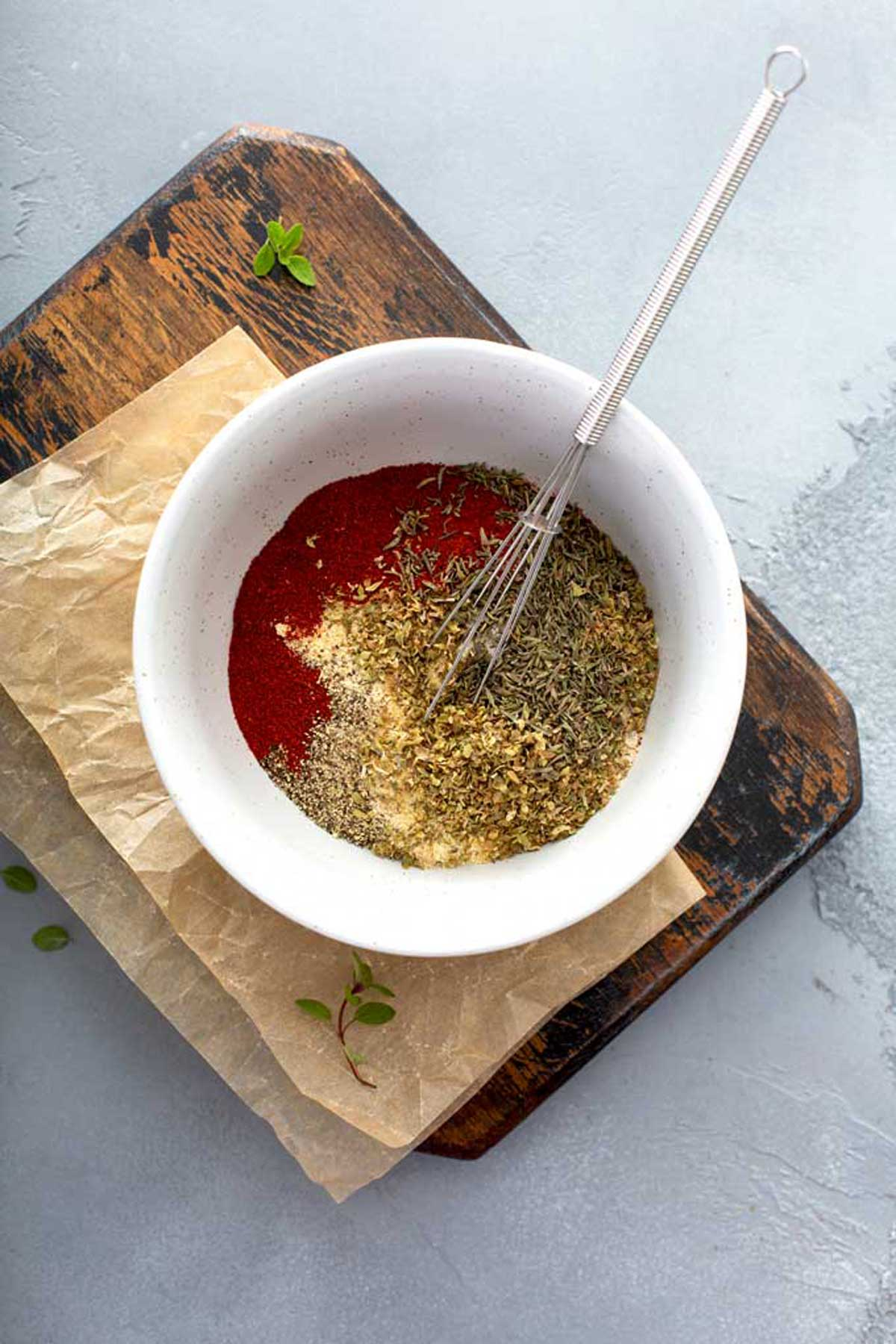 A combination of different spices getting whisked in a small bowl.