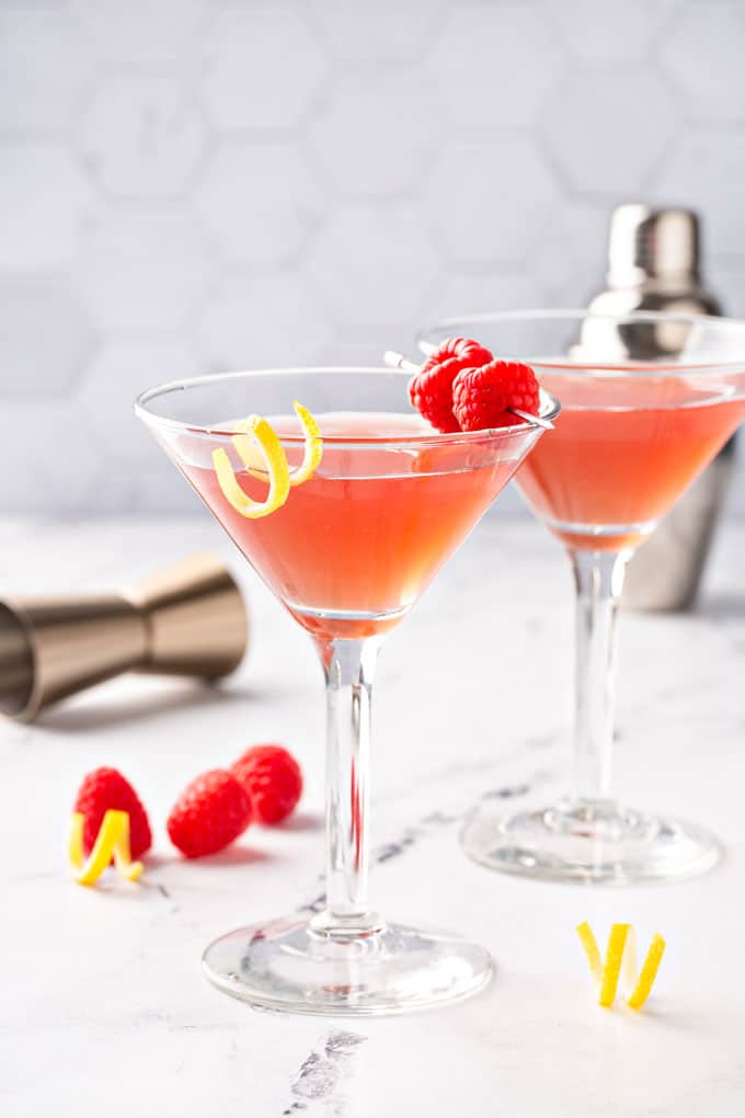 A couple of martini glasses with a lemon twist and raspberries.