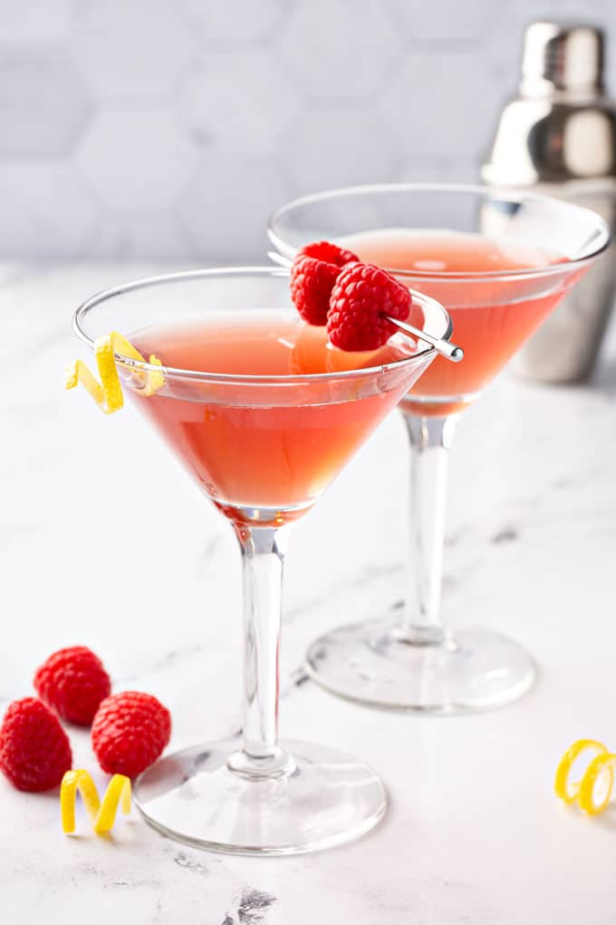 Two martini glasses with a martini garnished with fresh raspberries and a lemon twist.