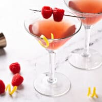 A couple of glasses with French martini garnished with braspberries