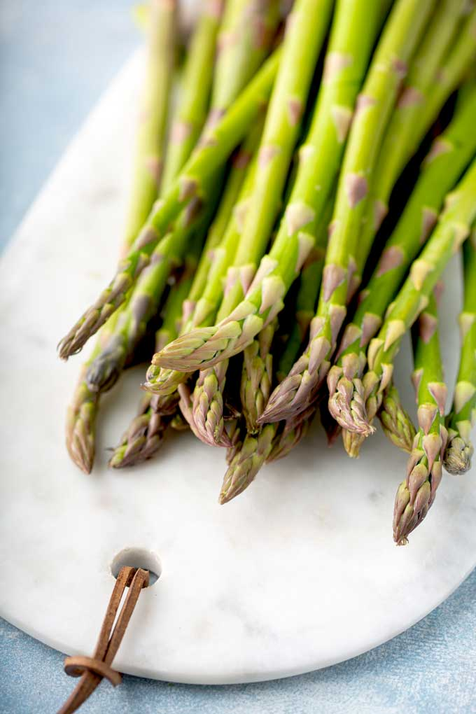 Fresh raw asparagus on a white marble board