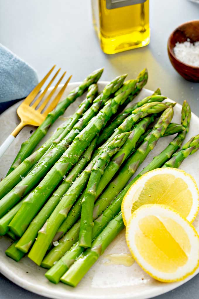Cooked asparagus on a plate served with lemon slices