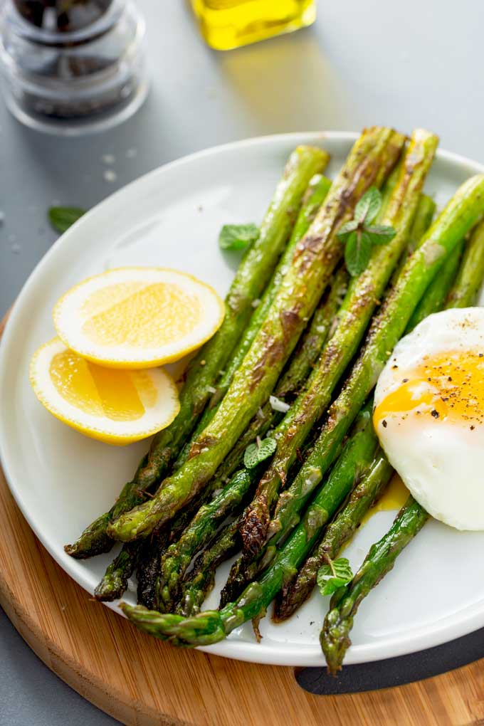 Pan seared asparagus served with a fried eggs on a white plate