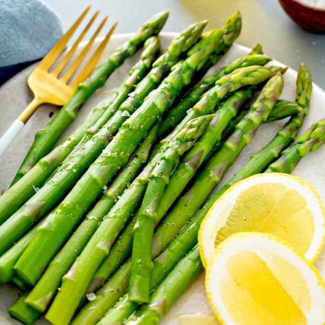 Cooked asparagus served with lemon on a plate.