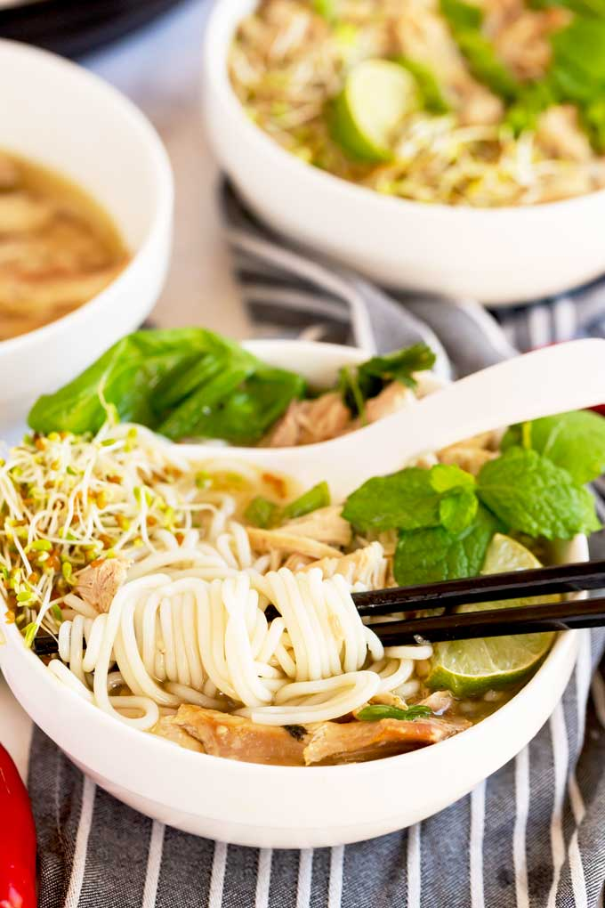 Noodles wrapped around chopsticks over a bowl of chicken pho