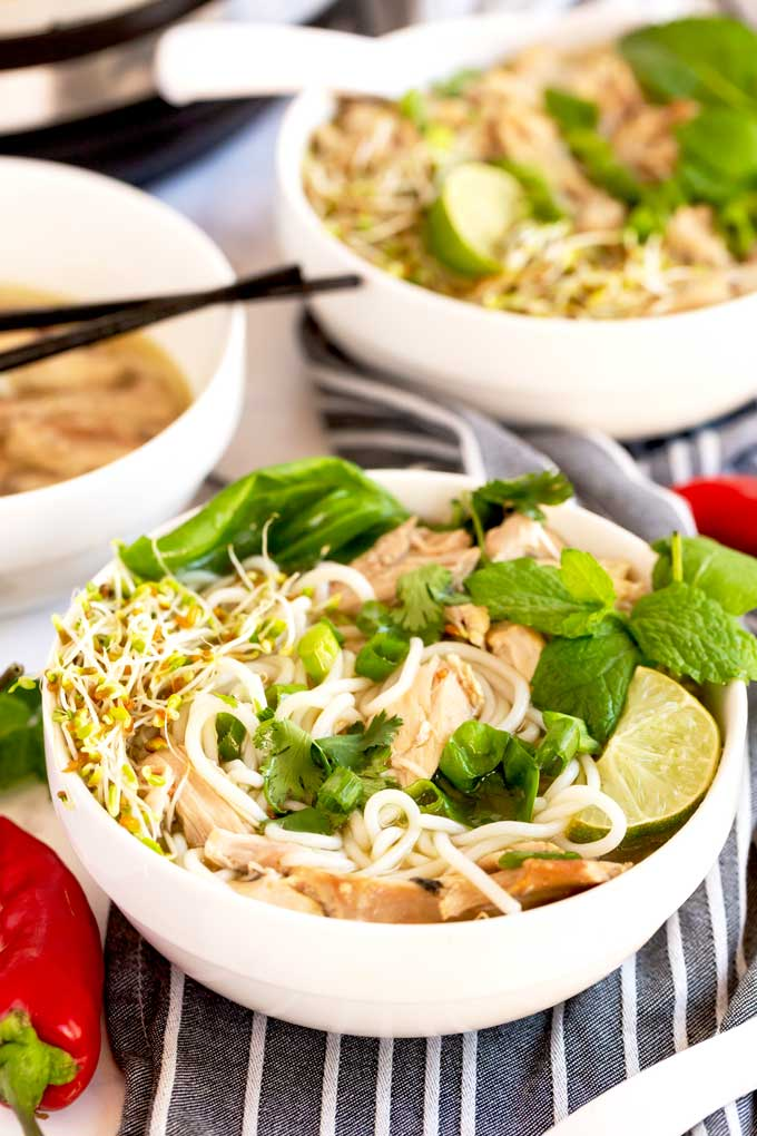 Bowl of Vietnamese soup Pho topped with fresh herbs