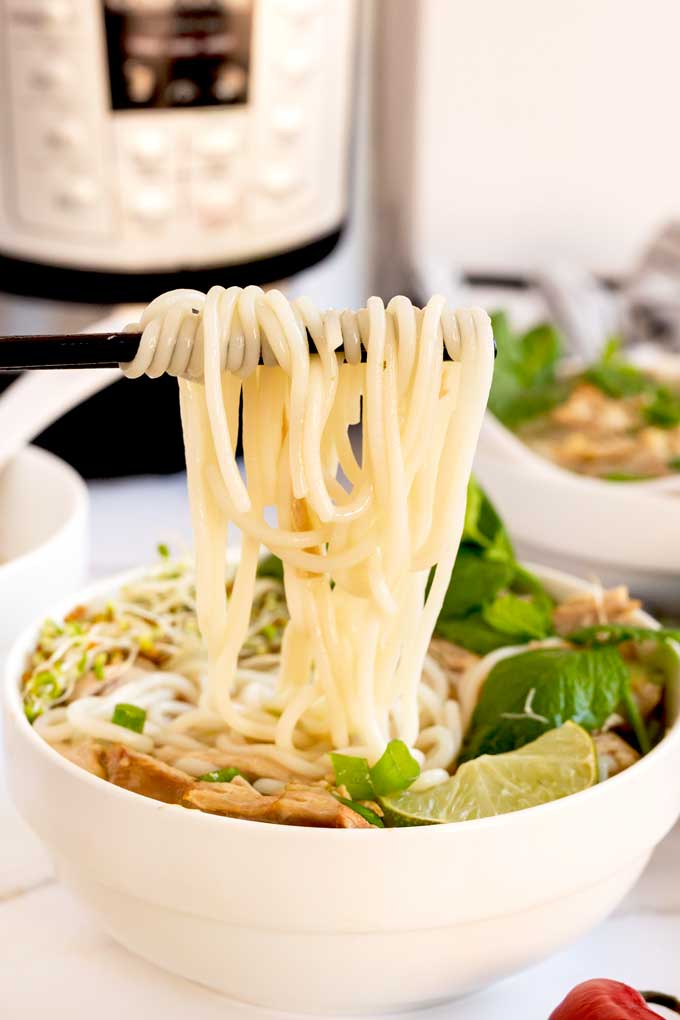 Noodles lift from a bowl of soup.