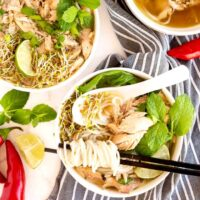 Bowls of Chicken Pho soup with toppings.