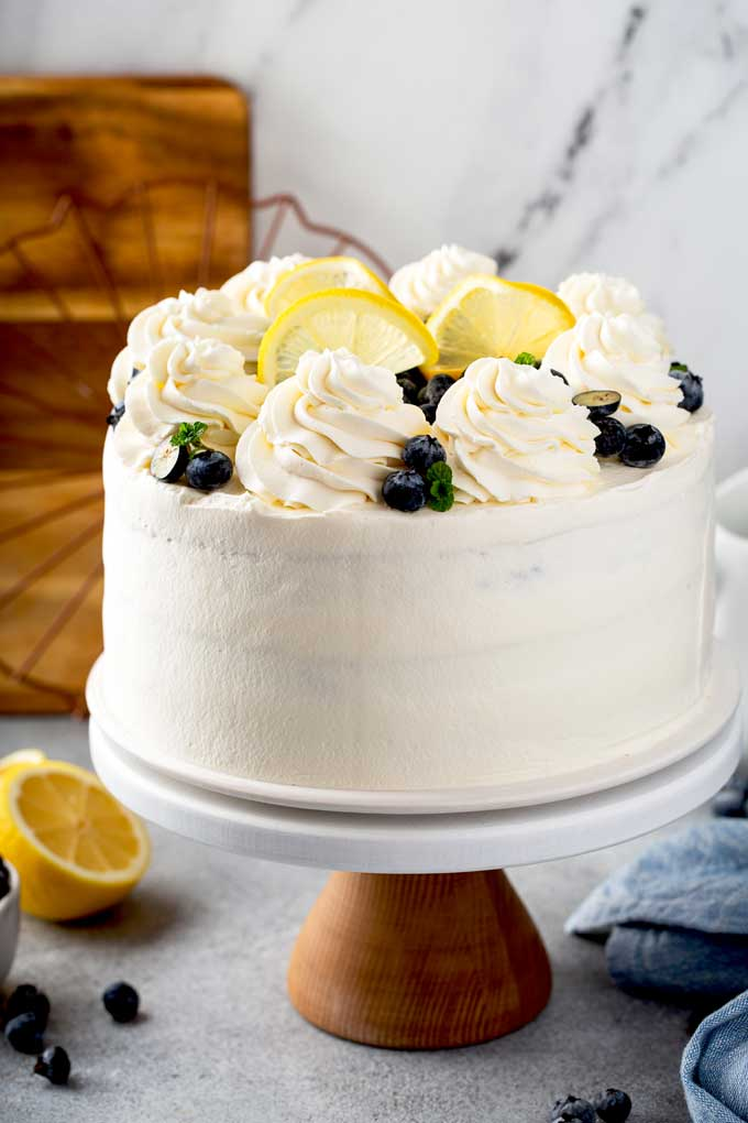 A cake covered in whipped mascarpone frosting on a cake plate.