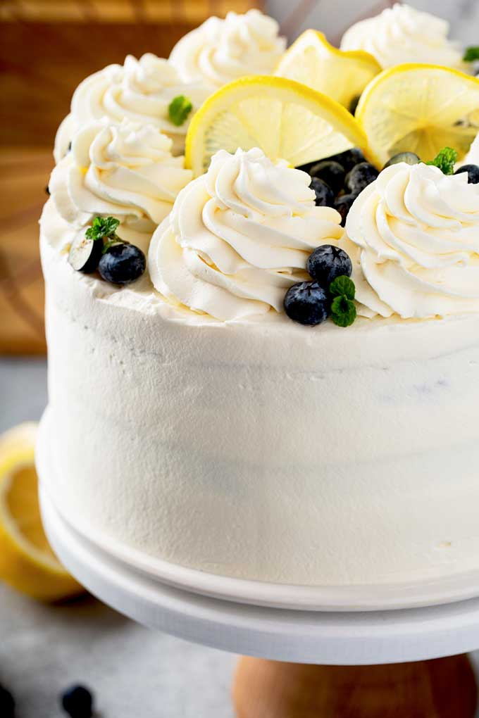 Close up view of lemon cake with whipped mascarpone frosting on a cake platter