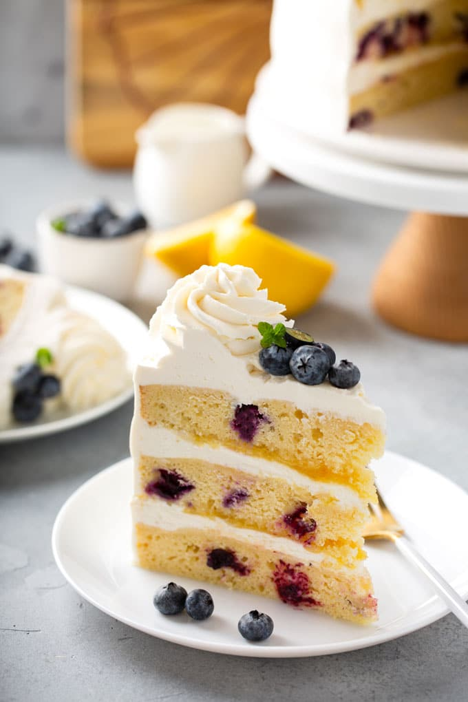 A slice of layered cake on a white plate garnished with blueberries