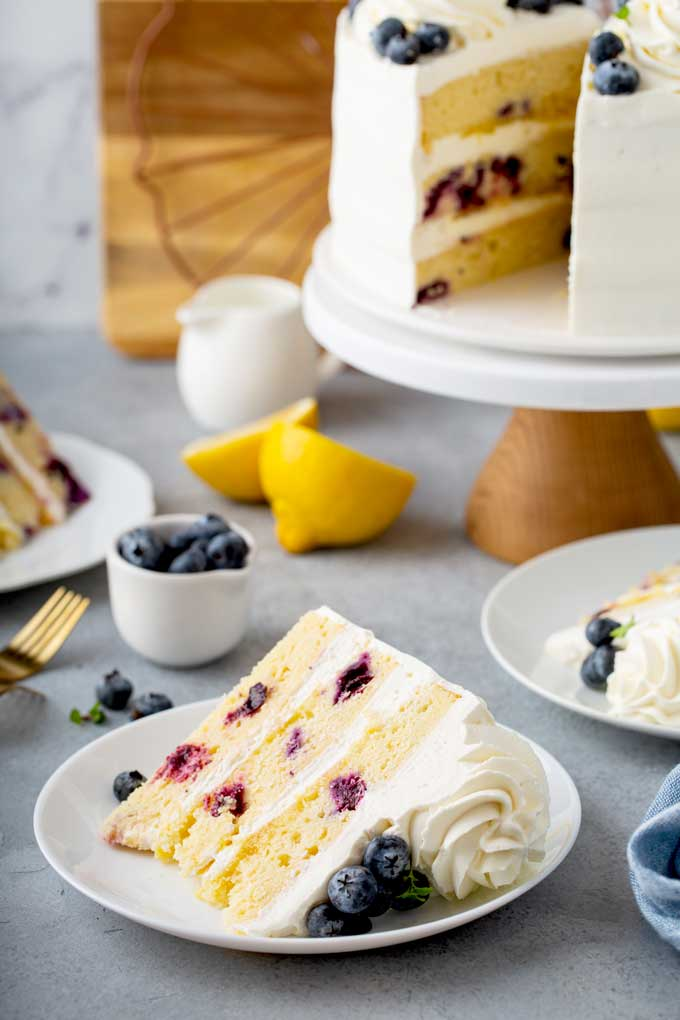 A sliced of blueberry and lemon cake next to whole layered cake on a gray surface